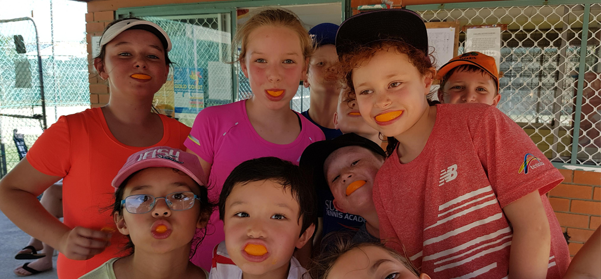 tennis holiday camps kids with oranges